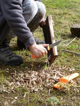Whittling with knife during bushcraft session